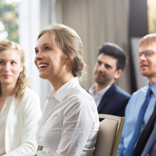 Young businesswoman and her male and female colleagues smiling, sitting and watching presentation in conference room