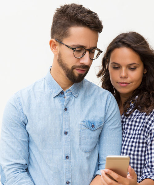 Focused couple reading message on cellphone screen. Young woman in casual and man in glasses in glasses posing isolated over white background. Mobile phone using concept